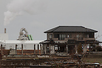 Tsunami damaged houses in front of an incineration plant that disposes of tsunami debris inside the Fukushima exclusion zone, Namie, Fukushima, Japan. Wednesday March 9th 2016. The Great East Japan Earthquake on March 11th 2011 was followed by a massive tsunami that levelled much of the Tohoku coast in north east Japan, killing around 18,000 people and causing meltdowns and explosions at the Fukushima Daiichi nuclear power station leading to the contamination and evacuation of a 20 kilometre exclusion zone around the plant.