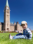 Smiling child sitting on grass in front of The Parliament Building in Ottawa. Ontario, Canada springtime scenic.
