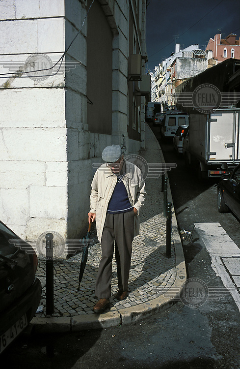 An elderly man walks down a street in the historic Alfama district of the city.