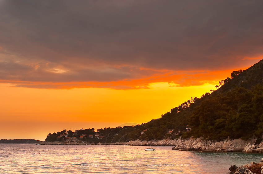 The Brna bay at sunset, bright orange sky, sky reflected in the sea water. Holiday homes on the hillside. Bright orange fiery sky. Prizba village. Korcula Island. Prizba, Riva Apartments, Danny Franulovic. Korcula Island. Dalmatian Coast, Croatia, Europe.