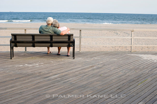 Retired senior couple relaxing on boardwalk bench