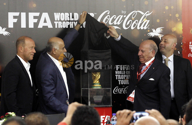 Palestinian businessman Zahi Khouri (2ed R) unveils the FIFA World Cup trophy as Palestinian Football Association chairman Jibril Rajoub (2ed L) applauds during the first stop of the FIFA World Cup Trophy Tour in the West Bank city of Ramallah on November 10, 2013. The trophy, 36.8 cm high made of Solid 18-carat gold, will travel through 89 countries in 267 days. Photo by Issam Rimawi