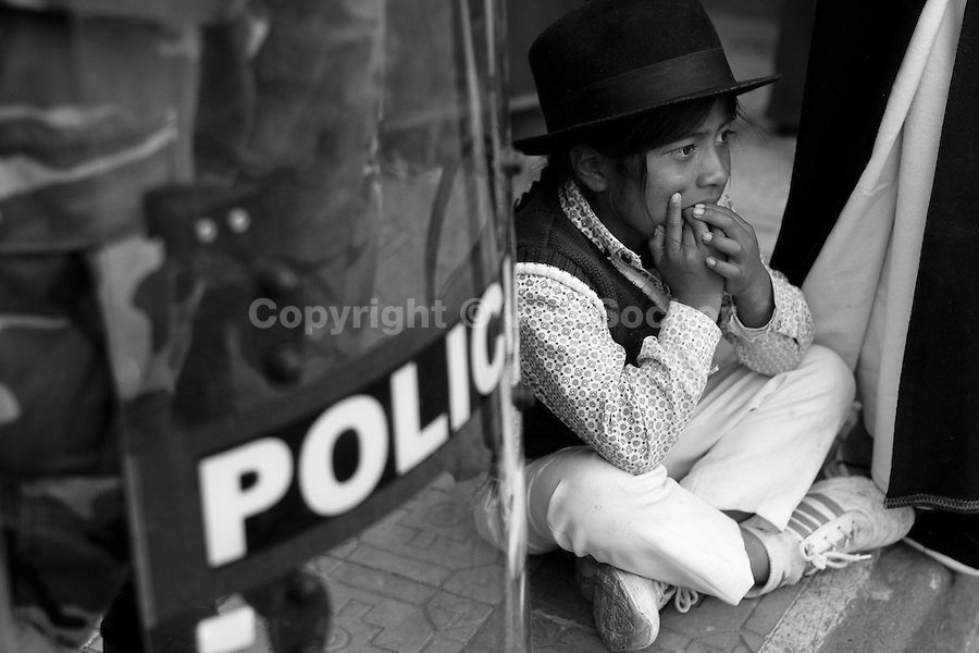 An Indian boy sits on the pavement next to a riot policeman during the Inti Raymi (San Juan) festivities in Cotacachi, Ecuador, 24 June 2010. 'La toma de la Plaza' (Taking of the square) is an ancient ritual kept by Andean indigenous communities. From the early morning of the feast day, various groups of San Juan dancers from remote mountain villages dance in a slow trot towards the main square of Cotacachi. Reaching the plaza, Indians start to dance around. They pound in synchronized dance rhythm, shout loudly, whistle and wave whips, showing the strength and aggression. Dancers from either the upper communities (El Topo) or the lower communities (La Calera), joined in respective coalitions, seek to conquer and dominate the square and do not let their rivals enter. If not moderated by the police in time, the high tension between groups always ends up in violent clashes.