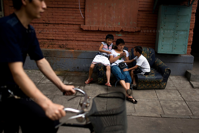Daily life continues as usual one street behind the Olympic facade in Beijing, China on Wednesday, August 6, 2008. The city of Beijing is gearing up for the opening ceremonies of the Olympic Games.  Kevin German