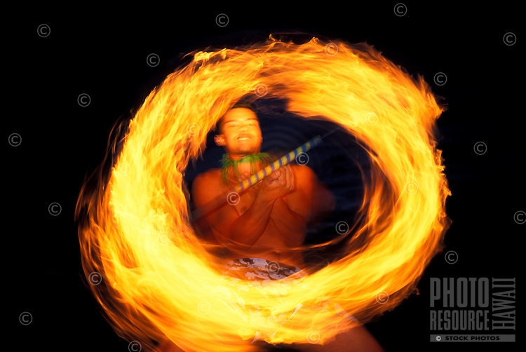 A local man does a fire dance with a torch on the Big Island.