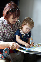 Polish grandmother reading to granddaughter age 63 and 2. Zawady Central Poland