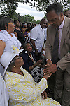 Reverend Jesse Jackson shakes hands with victims and relatives of people who buried their loved ones at the Burr Oak Cemtery before a prayer vigil across the street from Burr Oak in Alsip, Illinois on July 12, 2009.  On July 9, four managers and caretakers at the historically black Burr Oak Cemetery were arrested on charges of fraud and dismembering human remains; as families descended upon the site in search for answers, investigators were forced to close down the site as more dismembered human remains were discovered.