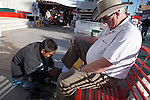 Tourist getting a shoe-shine in the central square, Los Algodones, B.C, Mexico.