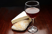 Still life photo of wine cheese and bread on rustic surface