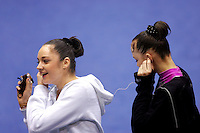 (L-R) Anna Bessonova and Galina Shyrkina of Ukraine share the same mp3 player and happy moments listening to the soundtrack to their gala exhibition at San Francisco Invitational on February 11, 2006. Bessonova won All-Around competition. (Photo by Tom Theobald)