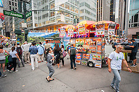 A hot dog vendor on the busy corner outside Bryant Park in Midtown Manhattan in New York on Monday, July 11, 2016. (© Richard B. Levine)