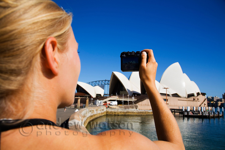 A woman photographs the Sydney Opera House.  Sydney, New South Wales, AUSTRALIA