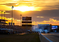 Mar 16, 2018; Gainesville, FL, USA; NHRA top fuel driver Antron Brown (right) does a burnout alongside Scott Palmer as the sun sets during qualifying for the Gatornationals at Gainesville Raceway. Mandatory Credit: Mark J. Rebilas-USA TODAY Sports
