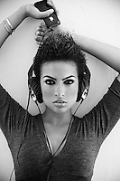 Femail leaned against a wall with an iphone and headphones listening to music with a mohawk