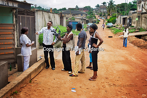 Actors Adaobi Enekwa and Dr. Keiggy Ogarekpe, director of photography Osmeka Onwuegbuzia, and film director Ola Orlando Shoyinka (left to right) shooting a scene of a Nollywood movie in the suburbs of Lagos. The street is not closed to traffic and people can freely pass by while the film is shot.
