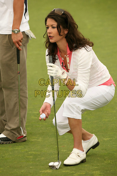 CATHERINE ZETA-JONES.9th Annual Michael Douglas & Friends Celebrity Golf Event at the Trump National Golf Club, Rancho Palos Verdes, California, USA..April 29th, 2007.sport full length white pink striped stripes top cropped beige trousers beige club glove kneeling crouching .CAP/ADM/BP.©Byron Purvis/AdMedia/Capital Pictures