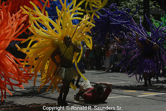 PHOTOG LAYS on GROUND to GET a BETTER SHOT of COLORFUL BALLOONS WHICH SURROUND AFRICAN SUPPORTER PARTICIPATING in GAY PRIDE PARADE<br /> (16)