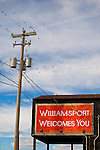 Telephone pole, starlings and Williamsport Welcomes You sign.