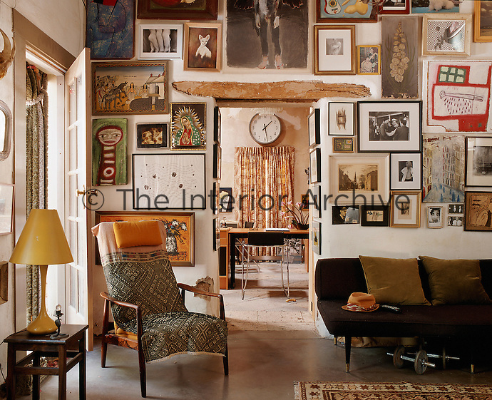 The adobe walls of the living room display a quirky collection of artwork