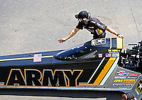 Mar 20, 2016; Gainesville, FL, USA; A crew member guides NHRA top fuel driver Tony Schumacher towards the starting line  during the Gatornationals at Auto Plus Raceway at Gainesville. Mandatory Credit: Mark J. Rebilas-USA TODAY Sports
