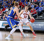 SIOUX FALLS, SD: MARCH 6: Matt Mooney #13 from the University of South Dakota drives against Reed Tellinghuisen #23 from South Dakota State University during the Summit League Basketball Championship on March 6, 2017 at the Denny Sanford Premier Center in Sioux Falls, SD. (Photo by Dave Eggen/Inertia)