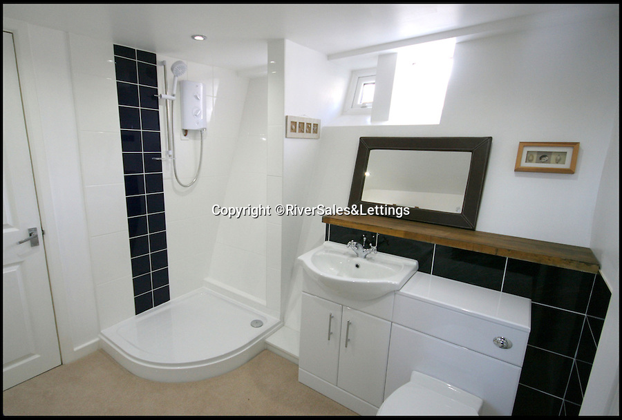 BNPS.co.uk (01202 558833)<br /> Pic: RiverSales&Lettings/BNPS<br /> <br /> ****Please use full byline****<br /> <br /> Ensuite.<br /> <br /> A 100-year-old barge once used to ship cargo up and down the River Thames has been transformed into a plush four-bedroom house that is now on the market for £450,000.<br /> <br /> The 90ft boat was salvaged from the banks of Thames in the 1970s and turned into a floating dormitory for schoolchildren at an outdoor activity centre.<br /> <br /> But it has since been given a complete makeover and now looks more like a cosy country cottage than a boat.<br /> <br /> The two-storey houseboat runs off mains electricity, has wifi access, electric heating, and hot water, and it also has a reserve water tank stored in its funnel.<br /> <br /> And buyers can count the picturesque River Hamble near Southampton, Hants, as their back garden.