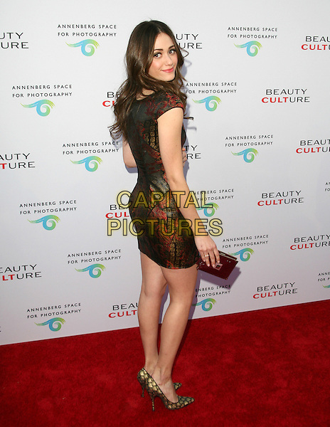 EMMY ROSSUM.at The opening of BEAUTY CULTURE, a photographic exploration of how feminine beauty is defined, challenged and revered in modern society held at Annenberg Space for Photography in Century City, California, USA,.May 19th 2011..full length red shiny print dress clutch bag brown pointy shoes gold  back over shoulder rear behind                                                                   .CAP/RKE/DVS.©DVS/RockinExposures/Capital Pictures.