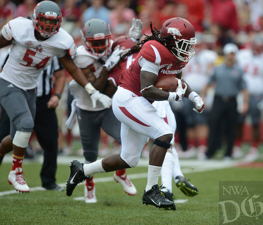 STAFF PHOTO ANTHONY REYES • @NWATONYR<br /> Alex Collins, Razorbacks running backs, breaks through the line of scrimmage against Nicholls State in the first quarter Saturday, Sept. 6, 2014 at Razorback Stadium in Fayetteville.
