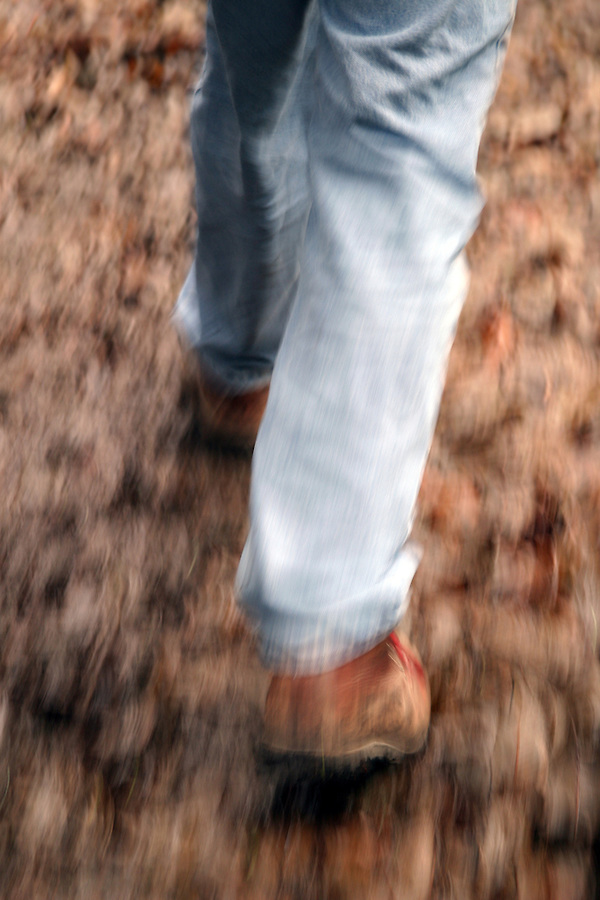 Man's legs with hiking boots walking on leaf covered ground