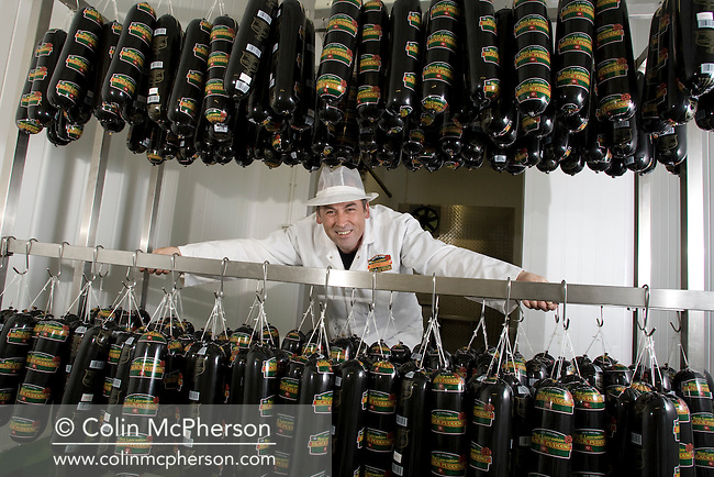 Champion black pudding maker Andy Holt pictured with racks of traditional Bury black puddings. Mr Holt's company, R. S. Ireland, is based in Haslingden, Lancashire, employing around 15 people making over 300 tonnes of black pudding each year.
