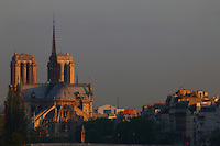 Paris Right Bank: A view from faraway of the back of the church of Notre Dame in Paris, with the fa&ccedil;ades of some typical buildings, in the sunrise light.<br />