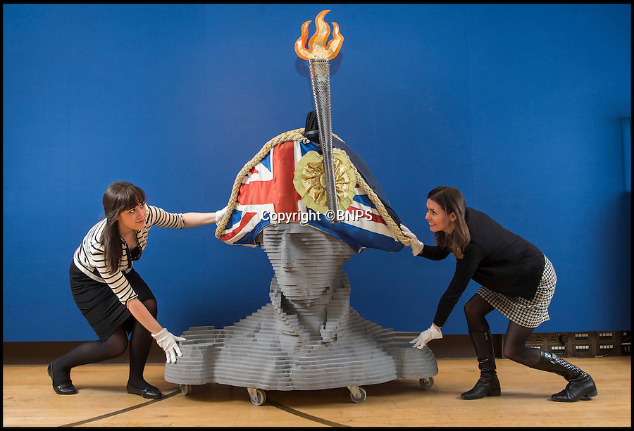 BNPS.co.uk (01202 558833)<br /> Pic: PhilYeomans/BNPS<br /> <br /> England expects...Christies staff carefully wheel in the huge hat.<br /> <br /> If you want to get ahead get a hat - £12,000 could secure you a unique piece of British sporting and military history with the sale of the Sylvia Fletcher designed hat that sat on the top of Nelson's column during the 2012 Olympics in London. <br /> <br /> The unusual item is part of the 'Style and spirit' sale at Christies this week and includes an original Olympic torch and wooden bust of the great naval hero.<br /> <br /> Unfortunately, being 6ft high and nearly 4ft wide, it won't be possible to wear the unique design, but it could be the ultimate 'statement piece' for a modern home.