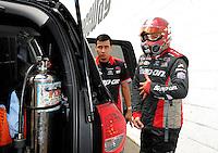 Jun. 2, 2012; Englishtown, NJ, USA: A crew member assists NHRA funny car driver Cruz Pedregon during qualifying for the Supernationals at Raceway Park. Mandatory Credit: Mark J. Rebilas-