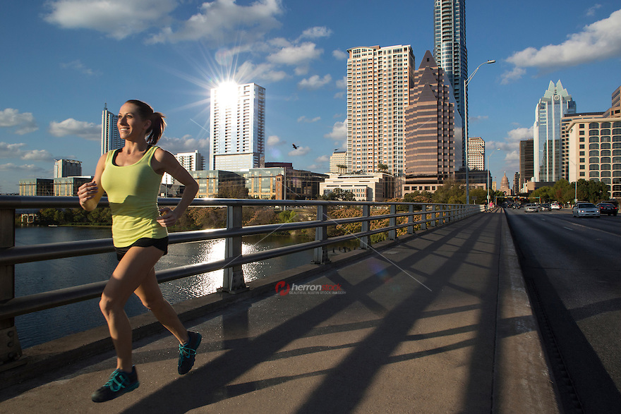 Running woman. Runner jogging on the Congress Avenue Bridge. Female fitness model training with the Austin skyline and Texas State Capitol in background on a bright sunny day with blue skies.