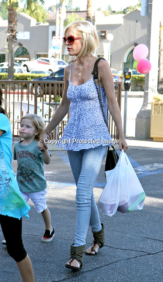 July 7th 2010 ..Los Angeles.Tori Spelling carrying her daughter as she goes shopping at PETCO. Mrs. Spellings kids Liam McDermott & Stella Doreen played with animals inside while Tori shopped around for doggy toys & reptile cages Tori was wearing weird sandals with brown fabric around them & red  heart sunglasses. ...AbilityFilms@yahoo.com.805-427-3519.www.AbilityFilms.com.