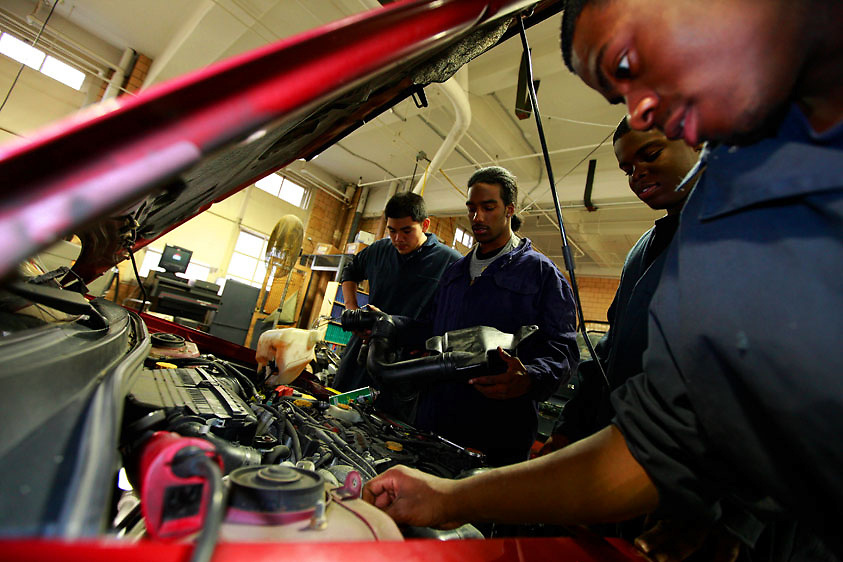 Automotive HS, Brooklyn, NY on Friday, January 22, 2010.  High school students have the opportunity to participate in a special program where they perform basic maintenance and repairs on privately owned cars at very competitive prices.  (l. to r.):  Students David Genis, 17; Dwayne Cadet, 18; Harry Cange, 17; and Joshua Smalls, 17, perform a tune-up on a car.