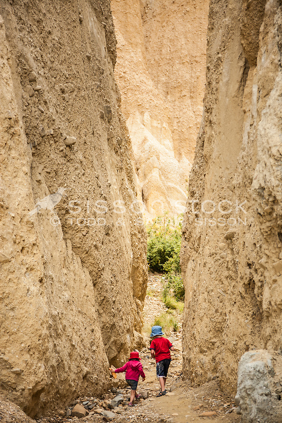 Children (girl 4 years boy 6 years) exploring the Clay Cliffs near Omarama, Canterbury, New Zealand - stock photo, canvas, fine art print