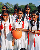 SRI LANKA, Asia, portrait of happy school girls in uniform holding a basketball