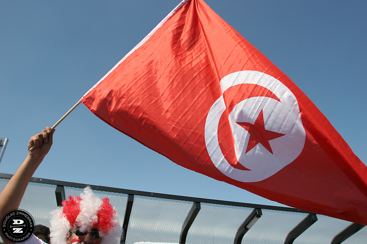 A Tunisian National Soccer Team fan waves a large Tunisian flag he walks to the Bayern-Munich arena  to watch Tunisia play their FIFA World Cup first round match against Saudi Arabia.  The two teams tied at 2-2.