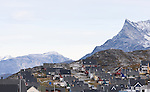 The city of Nuuk, Greenland, backdropped by mountains.