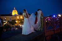 A bride and groom pose along the fortified wall of Cartagena, Colombia.