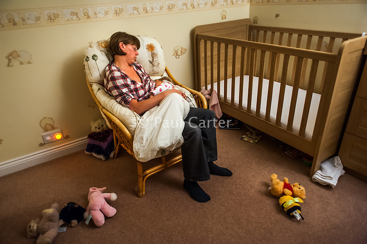 A mother dozes whilst breastfeeding her baby off to sleep in the evening.<br /> <br /> 13/09/12<br /> Hampshire, England, UK