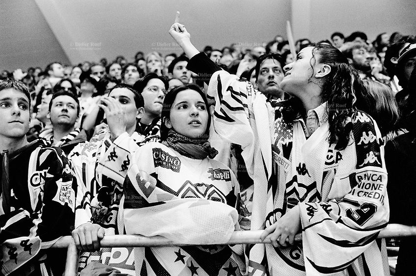 "Switzerland. Canton Ticino. Lugano. Resega ice rink. Final hockey game for the title of swiss championship. Lugano loses the game in overtime and the supporters are upset. A young woman is making an obscene gesture showing her middle finger ""Fuck off "" to the fans of the winning team. © 2001 Didier Ruef .."