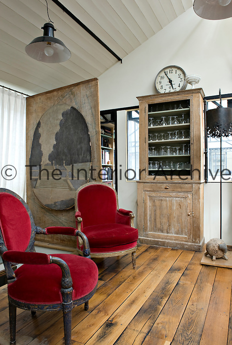 In the living room the floorboards are made of reclaimed railway sleepers and the armchairs have been recovered in modern velvet
