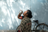 Rani barukaum, the SHG group leader drinks iJal water in the courtyard of her house in Ambedkar Nagar in Medak, Telangana, India.