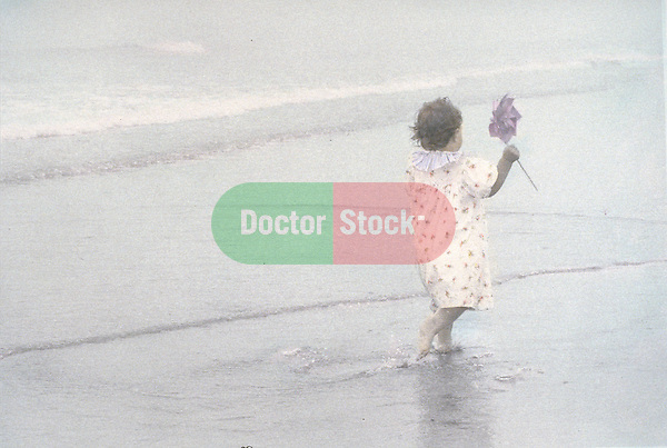 young child walking along shore on overcast day