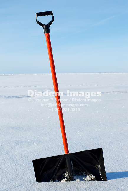 A snow shovel planted in the snow.