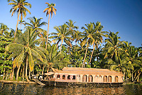 Aleppey, alappuzha, Kerala, India, April 2008. The houseboat, a converted kettuvalom rice barge, glides through the backwaters while daily life on the shore passes by. The backwaters of Kerala are reknowned for its rich history and its importance for the spice trade. Photo by Frits Meyst/Adventure4ever.com