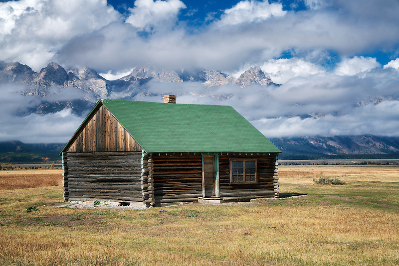 Bunckhouse at John Moulton Homestead with Teton Mountains and clearing clouds. Teton National Park, Wyoming