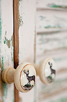A detail of a ceramic door handle with a deer painted on its surface